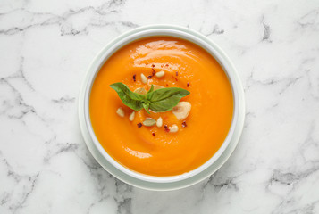 Delicious pumpkin soup in bowl on marble table, top view