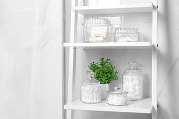 Cotton swabs and other hygiene products on shelving unit in bathroom