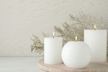Fotobehang - Beautiful Christmas composition with burning candles on white wooden background. Space for text