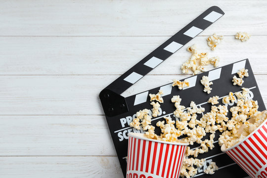 Clapperboard and popcorn on white wooden table, flat lay with space for text. Cinema snack