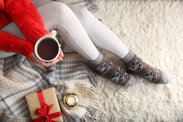 Fototapete - Woman wearing knitted socks on rug, top view. Warm clothes