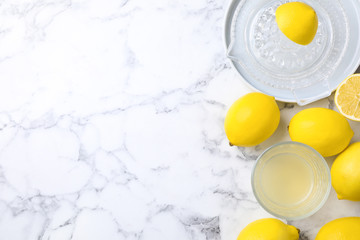 Flat lay composition with freshly squeezed lemon juice on white marble table. Space for text