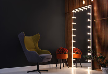 Large mirror with light bulbs in stylish room interior