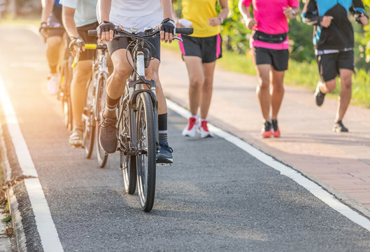Close up movement group of cyclists during ride bicycle with male runner jogging for exercise on the road park in sunset time healthy lifestyle concept