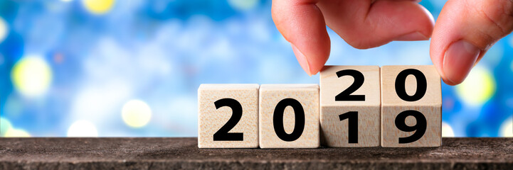 Hand Changing Date From 2019 To 2020 On Wooden Cube Calendar / New Year's Concept