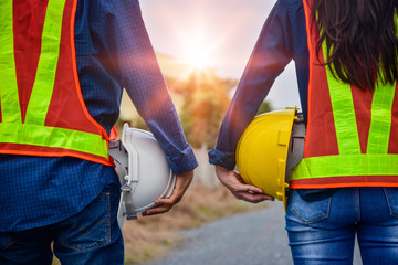 Man and Women Engineer holding hardhat safety Standing outdoor Teamwork management project