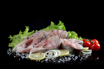 fish steaks with lettuce spices and tomatoes on a black background