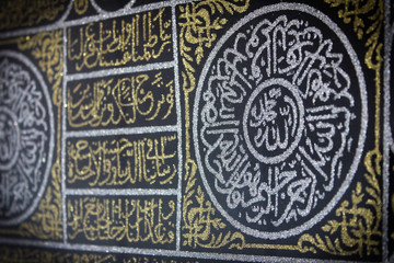 close up golden arabic calligraphy in black silk cloth kiswah cover of holy kaaba's door