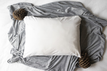 Plain white pillowcase on a grey and white textile background with pine cones - winter Christmas cushion mockup