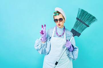 Cleaning Lady Fun. Elderly funny housewife fooling around with a broom. Full body isolated blue. Comical cleaning lady, old woman funky