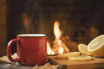 Red mug with hot tea with lemon in front of a burning fireplace, comfort and warmth of the hearth concept