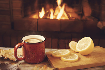 Photo sur Aluminium The Red mug with hot tea with lemon in front of a burning fireplace, comfort and warmth of the hearth concept