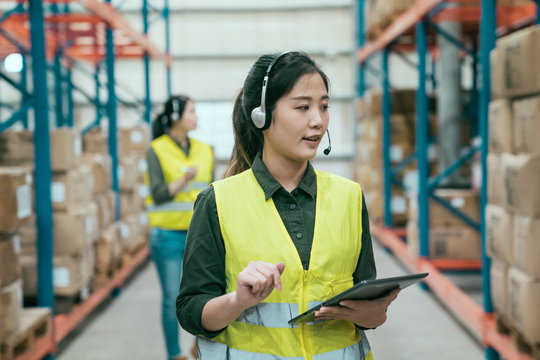 young lady business woman wearing headset talking with company and holding mobile digital tablet pad looking at stock goods checking order parcel. bokeh female colleague standing in back in warehouse