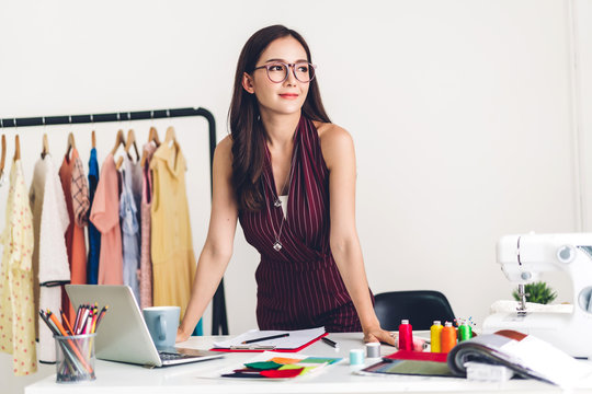 Smiling asia woman fashion designer working with laptop computer at workshop studio