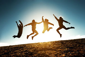Four jumping silhouettes friends against sun