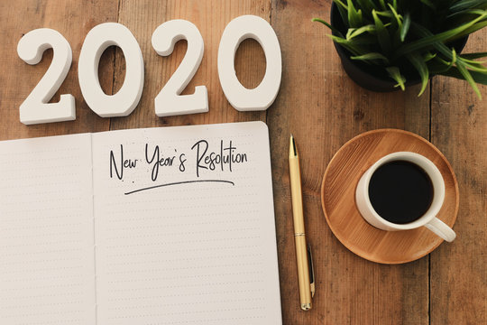 Business concept of top view 2020 year's resolution list with notebook, cup of coffee over wooden desk
