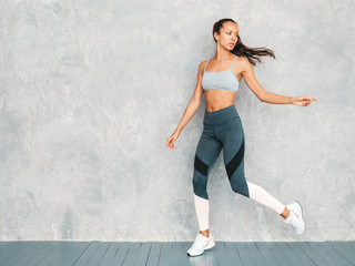 Portrait of fitness woman in sports clothing looking confident.Young female wearing sportswear.Beautiful model with perfect tanned body.Female jumping in studio near gray wall