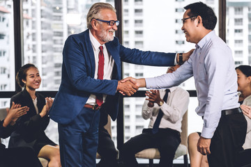 Image two business partners in elegant suit successful handshake together standing in front of...