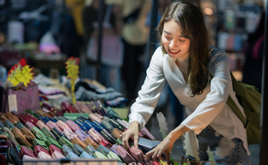Travel woman on night street market, clothes shopping concept