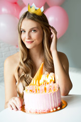 Happy pretty girl with cream cake and pink balloons at birthday party.  Barbie style. Princess.  16 years old girl.