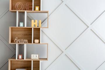 Stylish rack with decor near grey wall