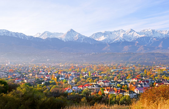Panoramic view of the upper part of Almaty city on the background of mountains in autumn season; golden fall, beauty and greatness of Kazakhstan concept