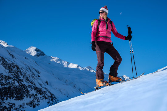 Young woman with skis in winter mountains