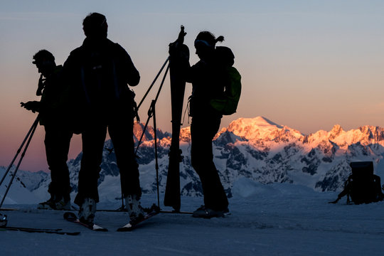 Silhouettes of skiers at dawn