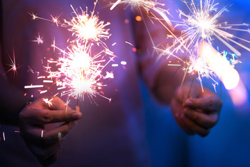 Hand of woman holding firework firework pyrotechnics and bokeh with blurry effect on the dark background for celebration concept