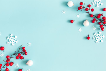 Christmas or winter composition. Snowflakes and red berries on blue background. Christmas, winter,...