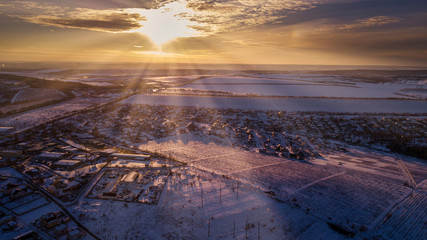Top view of city suburbs or small town nice houses on winter sunset on cloudy sky background. Aerial drone photography concept.