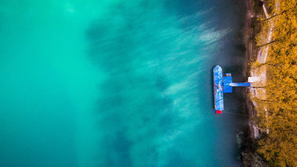 Foto auf Acrylglas Reef grun Emerald Green Lake with Colorful Boat. Aerial Drone Top Down Photo.