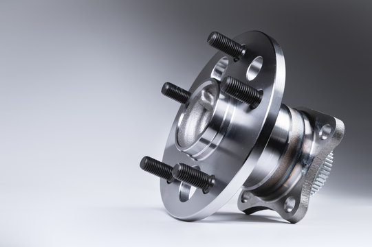 New Wheel hub assembly with bearing. This is part of the car suspension on a gray background with a gradient. The concept of new car parts