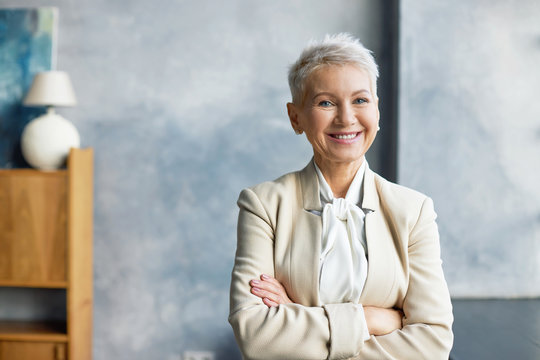 Portrait of successful attractive senior businesswoman with stylish short hairdo and confident smile posing in her modern office, keeping arms crossed on chest, wearing elegant beige formal suit