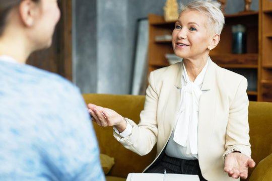 Attractive mature female HR director and job candidate at interview, having lively discussion. Confident middle aged woman in formal wear gesturing emotionally, interviewing applicant in front of her