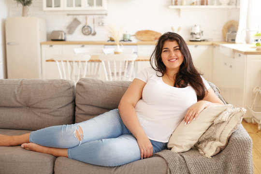 Portrait of positive young overweight brunette female sitting barefooted on gray sofa with legs outstretched wearing ripped jeans and white t-shirt looking at camera with happy cheerful smile