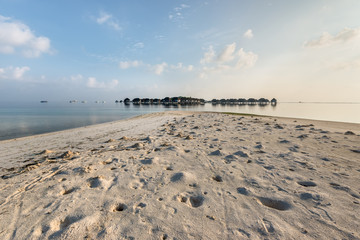 Water bungalows and sea in a tropical paradise island in Maldives. Sandbank with crab burrows in the foreground.