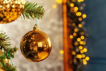 Beautiful golden bauble hanging from a Christmas tree