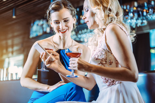 Two women in a bar looking at their mobile phone