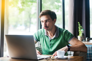Young funny businessman in green t-shirt sitting and looking at laptop display with stupid crazy face and crossed eyes. business and freelancing concept. indoor shot near big window at daytime.