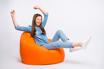 Profile side photo of delighted funky girl have rest sit big lounge armchair watch football world cup match see team win raise fists scream yeah wear casual outfit isolated white color background