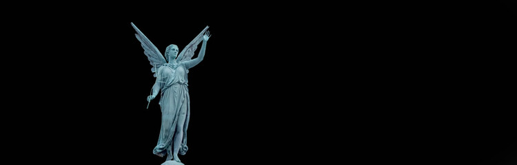 Wall Mural - Statue of an angel against black background