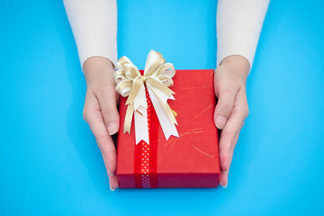 Close up female hand holding craft gift box as a present for Christmas, new year on blue background