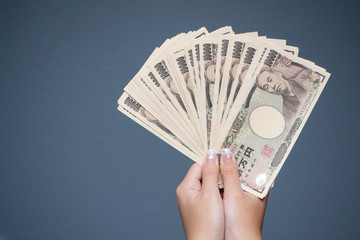 Close up female hand holding Japanese yen 10000 notes