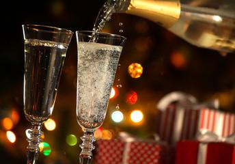Beautiful splash of champagne glasses and Christmas lights