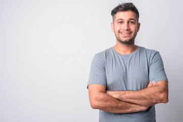 Portrait of happy young Persian man smiling with arms crossed