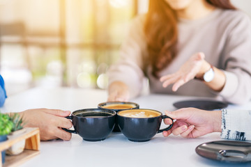 Closeup image of people enjoyed talking while drinking and clinking coffee cups on the table in cafe