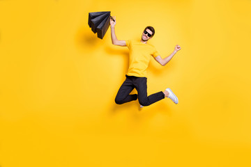 Full size photo of handsome guy jumping high holding shopping packages excited by low prices wear...