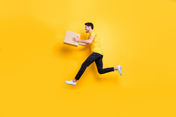 Full length photo of handsome guy jumping high holding big parcel box hurry move new apartments wear casual t-shirt pants isolated yellow color background