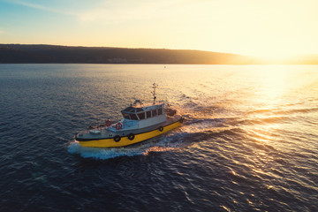 Patrol boat sailing at sunset in shining golden sea water